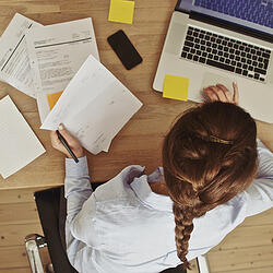 Woman at laptop with papers