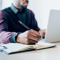 Man writing at laptop